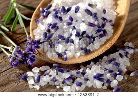 Lavender bath salt with blossoms on wooden spoon