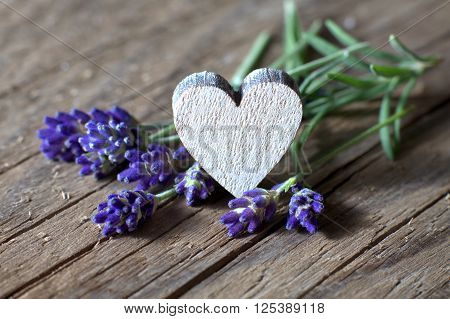 Bunsh of lavender flowers and a wooden heart with copy space