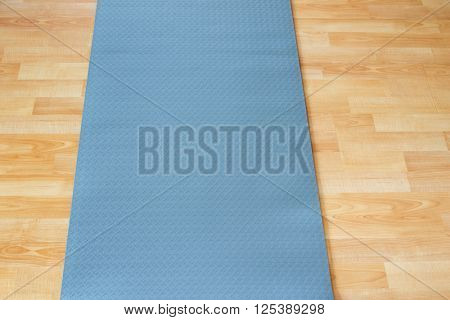 Thick anti slip blue fitness yoga practice or meditation mat made of PVC on yellow laminate wooden floor