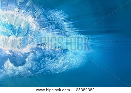 Underwater photo of ocean extreme wave breaking on tropical beach with spray foam ripples on water surface and bubbles pattern. Light blue color abstract background of clear sea surf with texture