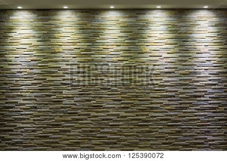 Stone wall with spotlights that illuminate from above
