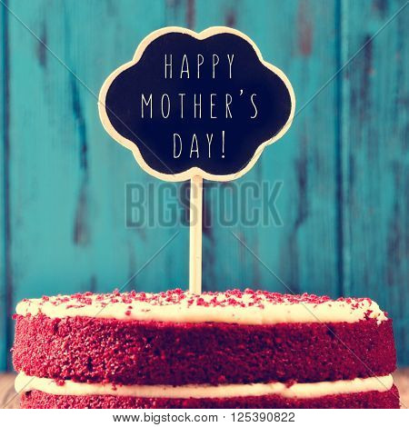 closeup of a red velvet cake topped with a chalkboard in the shape of a thought bubble with the text happy mothers day, against a blue rustic wooden background