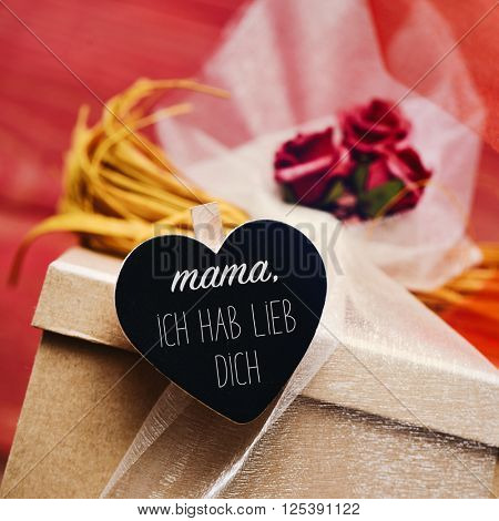 closeup of a gift box ornamented with flowers and tulle, and a heart-shaped chalkboard with the text mama ich hab lieb dich, I love you mom in German