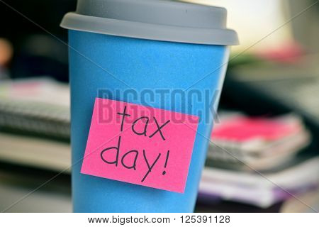 closeup of a blue coffee cup with red sticky note attached to it with the text tax day, in the office