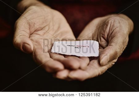 closeup of a piece of paper with the text happy mothers day in the hands of an old woman