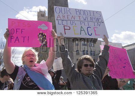 Asheville, North Carolina, USA - April 2, 2016: HB2 protesters display signs and hail passing cars on April 2, 2016 in downtown Ashevile, NC