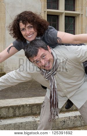 Couple Outside In The Countryside Have Fun On Piggy Back