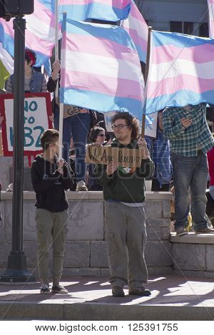 Asheville, North Carolina, USA - April 2, 2016: Crowd holds signs waves symbolic flags and protests the new North Carolina HB2 Law that restricts the rights of those who are gay or transgender in downtown Asheville, NC