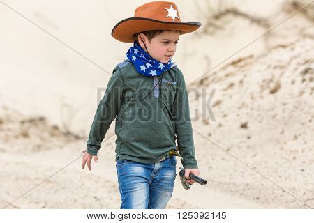 boy in a sheriff hat with a gun