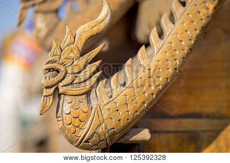 Wooden dragon figure on a small temple roof in Thailand
