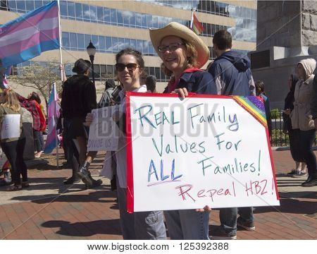 Asheville, North Carolina, USA - April 2, 2016: Women hold HB2 legislation protest signs calling for its repeal and for real family values for all families at a LGBT rally