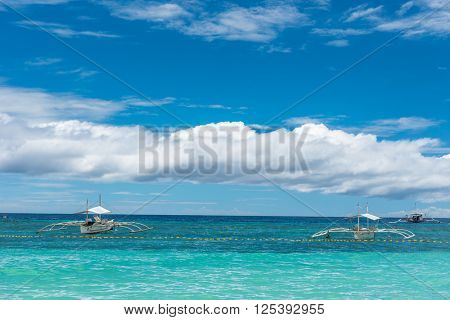 Tropical background view from Paglao island at Alona beach with traditional boats, blue sky and turquoise sea water, Travel Vacation at Philippines,