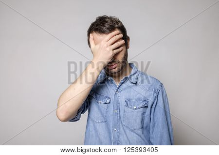 Portrait of worried man isolated on gray background