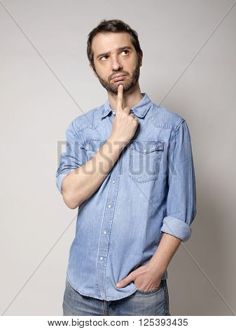 portrait of doubtful man on gray background