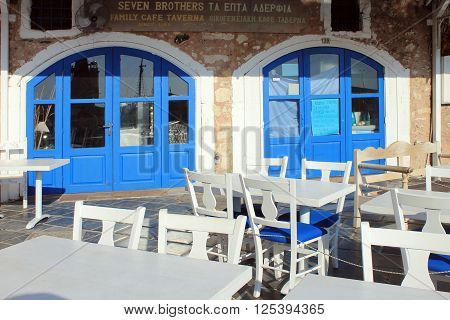RETHYMNO, GREECE - JULY 24, 2015: Outdoor restaurant with white and blue tables and chairs in the old Venetian port of Rethymno on Crete island in Greece