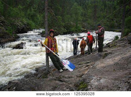 KOLA PENINSULA RUSSIA - AUGUST 09 - Men in the life vest examines threshold mountain river in Kola Peninsula on August 09 2008.