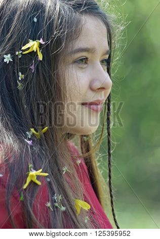 Beautiful girl with flowers in her hair in spring time