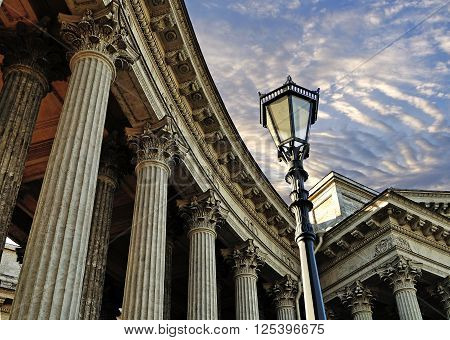 Facade details of Kazan Cathedral in Saint Petersburg Russia - colonnade and metal lantern against dramatic sunset sky