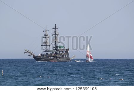 CAMYUVA KEMER TURKEY - JULY 14 2015: On the coast of Turkey widespread various marine activities. Among them walks on boats and yachts stylized pirate schooner