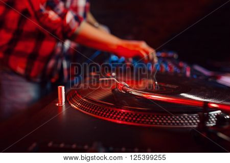 Cute dj woman having fun playing music on vinyl record deck at club party nightlife lifestyle. Vinyl record closeup