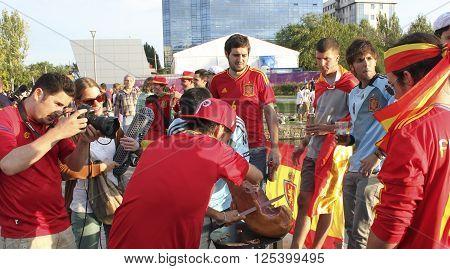 DONETSK UKRAINE - JUNE 27 2012: Unidentified Spanish soccer fans regale jamon before UEFA EURO 2012 match in Donetsk near Donbass Arena
