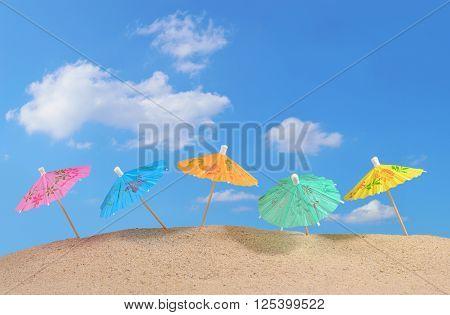 Cocktail Umbrellas On A Beach Sand