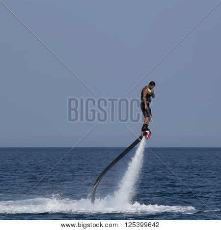 CAMYUVA KEMER TURKEY - JULY 12 2015: Unidentified Turkish man hovered above the water. Extreme water sports are increasingly popular on the beaches of Turkey