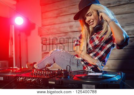 Cute dj woman having fun playing music on vinyl record deck at club party nightlife lifestyle** Note: Soft Focus at 100%, best at smaller sizes