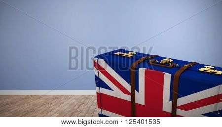 Great Britain flag suitcase against room with wooden floor