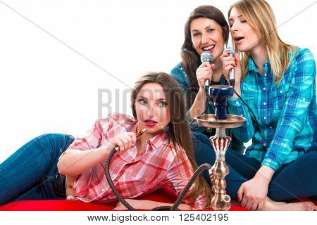 Portrait of three women. A party. Hookah. Karaoke