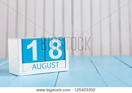 August 18th. Image of august 18 wooden color calendar on blue background. Summer day. Empty space for text.