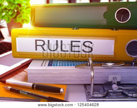 Rules - Yellow Office Folder on Background of Working Table with Stationery and Laptop. Rules Business Concept on Blurred Background. Rules Toned Image. 3D.