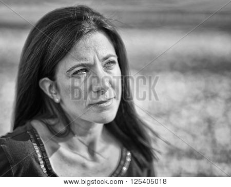 Sad beautiful woman outdoors against fall leaf background in black and white