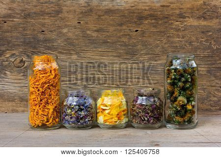 herbs and flower petals in glass jars on the background of the old wooden barn boards. with space for text. the concept of aromatherapy homeopathy alternative medicine