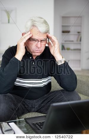 Portrait of a worried man trying to concentrate in front of a laptop computer