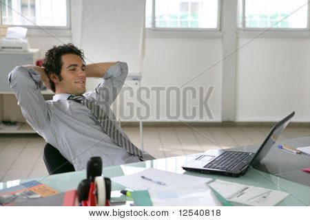 Portrait of a relaxed man in front of a laptop computer
