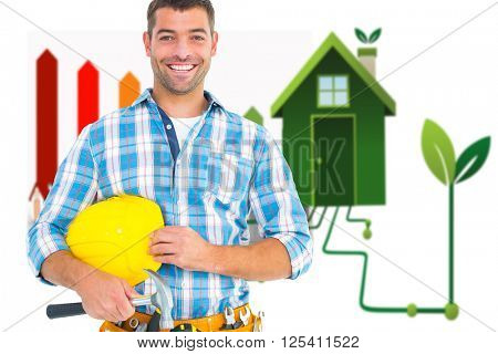 Smiling handyman holding hardhat and hammer against clean energy house