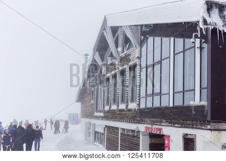 ROSA KHUTOR, RUSSIA - MARCH 27, 2016: View of chalet in the mist at Rosa Peak during the snowfall