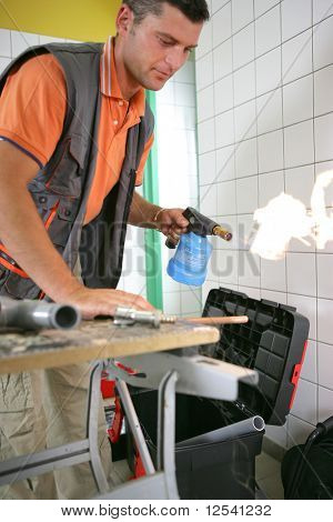Man warming a pipe in metal with a blowtorch