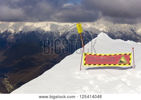 ROSA KHUTOR, RUSSIA - MARCH 31, 2016: Warning sign on Rosa Peak, scenery top view on snowy Caucasus mountains