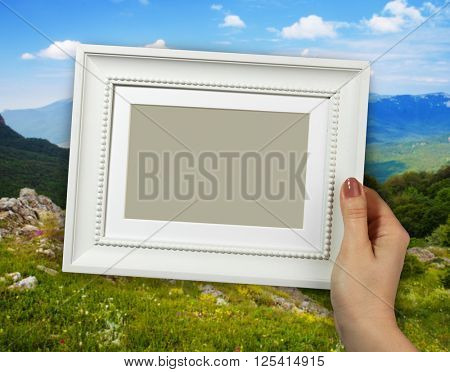 Wooden frame in beautiful woman hands on the Mountain background