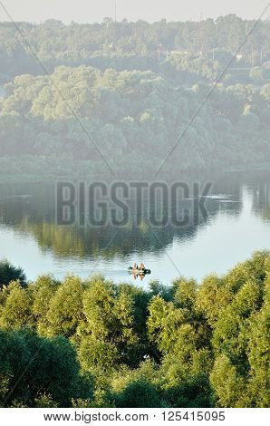 Aerial view of picturesque water landscape with fisherman boat on the river lit by soft morning sunlight