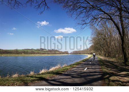Cyclist riding on a cycle path beside the river