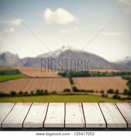 Wooden table against country scene with mountain