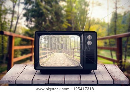 Retro tv against bridge with railings leading towards forest