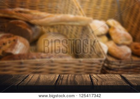 Wooden desk against baskets with breads freshly baked and tongs