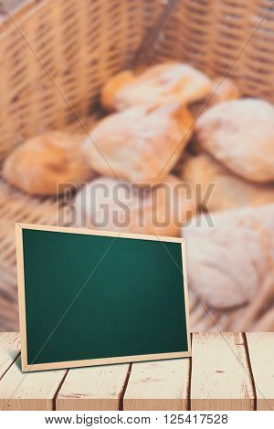 chalkboard against baskets with delicious breads and tongs