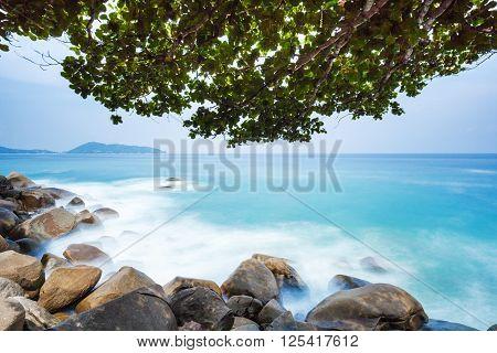 Long exposure of Kalim Beach in Phuket with boulders sea and deciduous tree