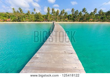Wooden pontoon in the turquoise tropical sea of Bang Bao Bay in Ko Kood island, Thailand .