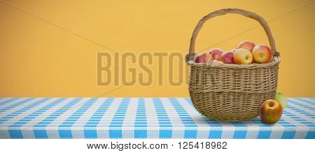 Basket of apples against orange background